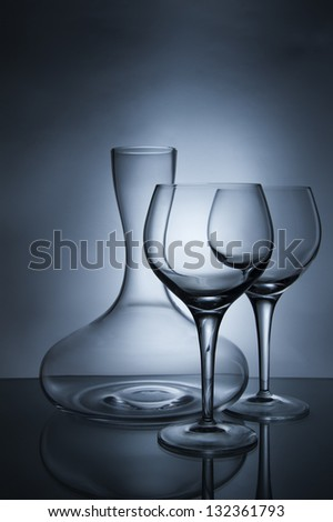 Two wine glasses and a decanter on a blue background - stock photo
