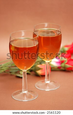 Two wine glasses and flowers at the background - stock photo
