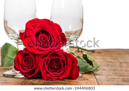 Two wine glasses with three red roses - stock photo