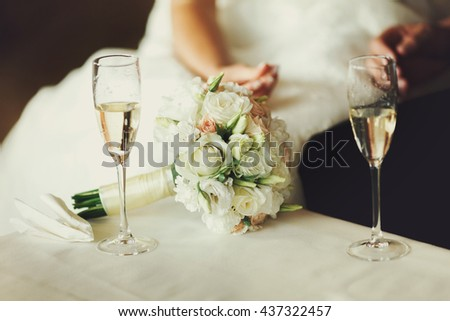 Two wineglasses with champagne stand on the table behind a wedding bouquet - stock photo