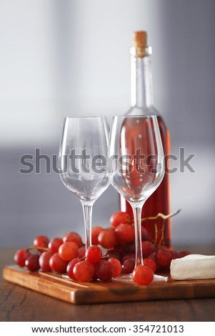 Two wineglasses with grape, cheese and bottle, still life - stock photo