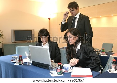 two woman and a man in a meeting room - stock photo