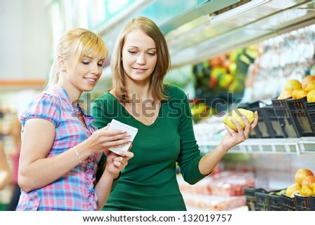 Two woman choosing bio food produces in fruits supermarket with shopping list - stock photo