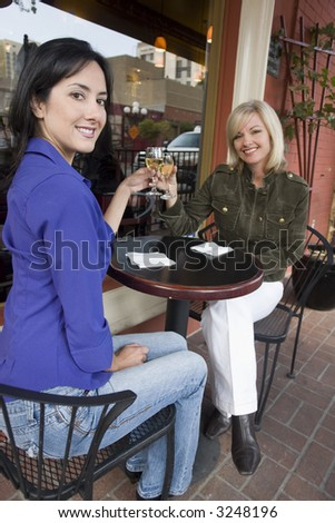 Two woman enjoying drinks outside - stock photo