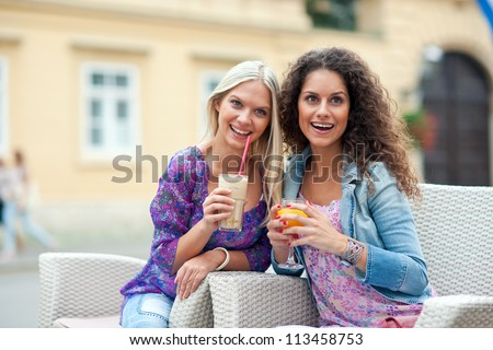 two woman friends at cafe having fun and talking - stock photo