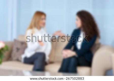 two woman friends on the sofa talking , blurred for presentation effect, abstract background - stock photo