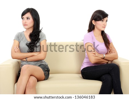two woman hates each other. sitting on the couch - stock photo