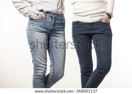 Two woman(model, girl, female) wearing blue denim pants(jeans, trousers), white shirts make a pose isolated white at the studio. - stock photo