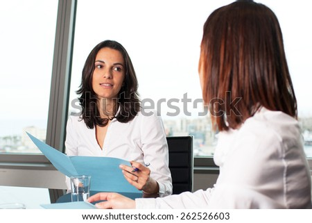 Two woman sitting at a table in office during job interview - stock photo