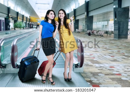 Two woman traveling with suitcase standing in airport - stock photo