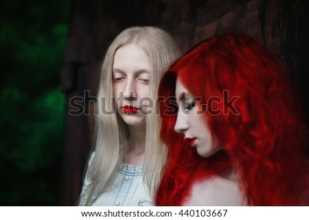 two women, a girl with curly red hair and a woman with long straight white hair, blonde, people with pale skin and blue eyes, style, fashion, friendship, love between women - stock photo