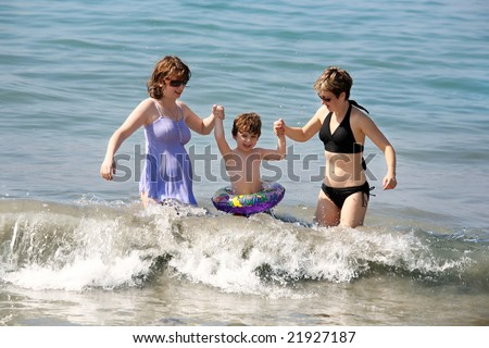 Two women and a baby playing in the ocean - stock photo