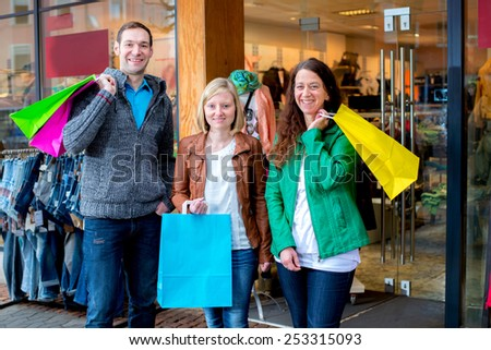 two women and a man in front of clothes shop - stock photo