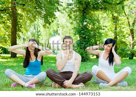 Two women and a man show three monkeys - stock photo