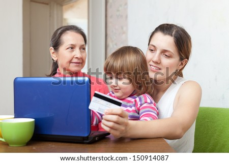Two women and child  paying by credit card in internet store at home - stock photo