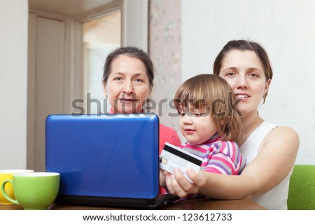 Two women and child shopping in internet from home, using laptop and paying with credit card - stock photo