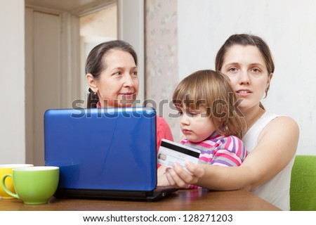 Two women and child shopping online in living room at home - stock photo