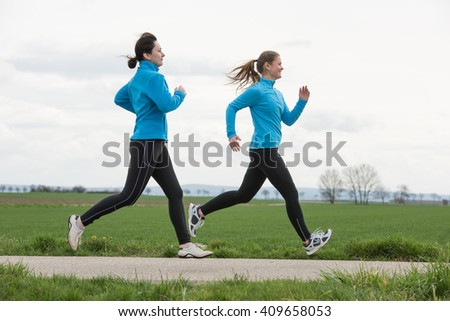 two women, 40 and 20 years old, jogging (running) outdoors - stock photo