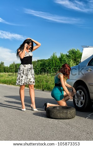 Two women are changing a tire on a road - stock photo