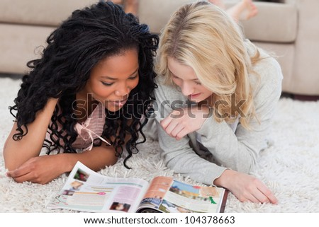 Two women are lying on the floor and reading a magazine - stock photo