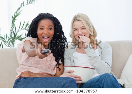 Two women are sitting down looking at the camera with popcorn and a television remote - stock photo