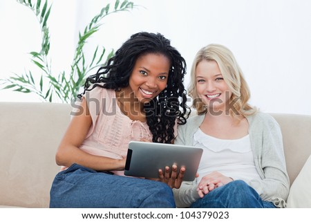Two women are smiling at the camera and have a tablet computer in front of them - stock photo