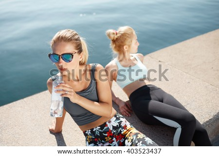 Two women athlete having break after running exercise. Athletic females resting on the beach after physical exercises. Blonde active girls enjoying break during running training outdoors on morning.  - stock photo