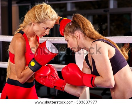 Two  women boxer wearing red  gloves to box in ring. Aggressive training. - stock photo