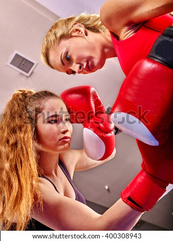 Two  women boxer wearing red  gloves to box in ring. Low point shooting. - stock photo