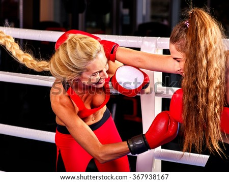Two  women boxer with long hair wearing red  gloves to box in ring. - stock photo