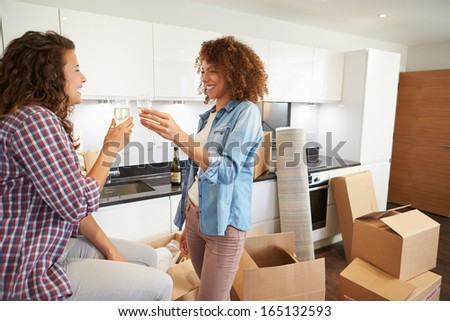 Two Women Celebrating Moving Into New Home With Champagne - stock photo