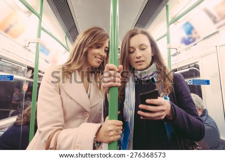 Two women commuting with tube in London. They are in their late twenties, both with long hair. They are looking at smart phone and holding at pole. - stock photo