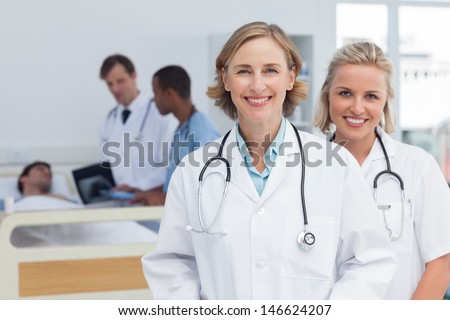 Two women doctors standing and looking at the camera in front of medical team and patient - stock photo