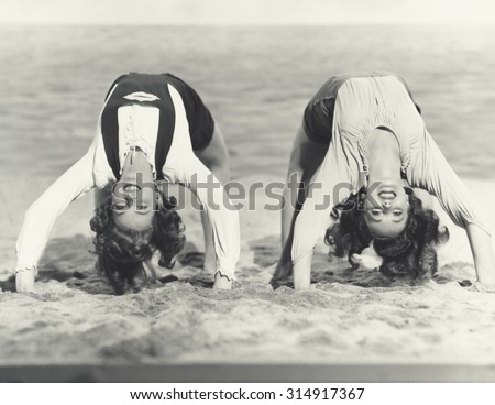 Two women doing backbends on the beach - stock photo