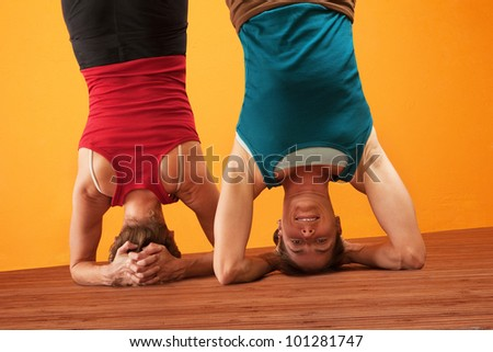 Two women doing headstands over yellow background - stock photo