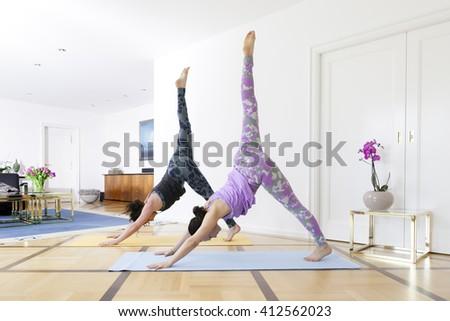Two women doing yoga at home down dog split pose - stock photo