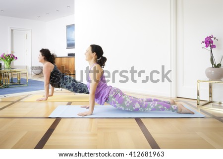Two women doing yoga at home upwards looking dog pose - stock photo