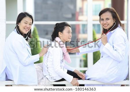Two women dotor checking lovely girl in hospital - stock photo