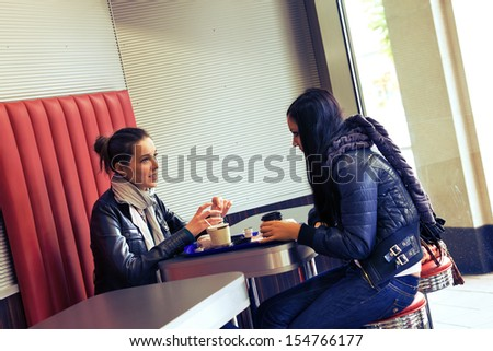two women drinking coffee and talking in the cafe - stock photo