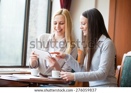 Two women drinking coffee and using digital tablet in cafe - stock photo