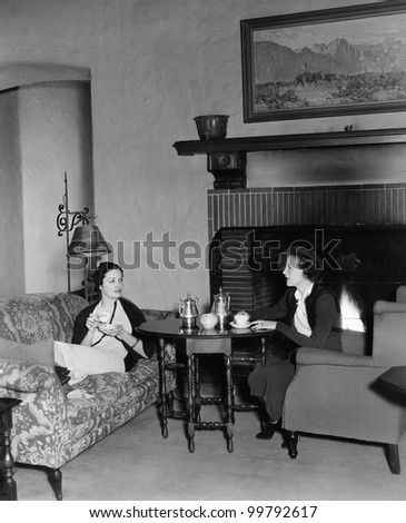 Two women drinking tea and talking - stock photo