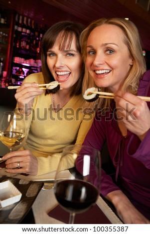 Two Women Enjoying Sushi In Restaurant - stock photo