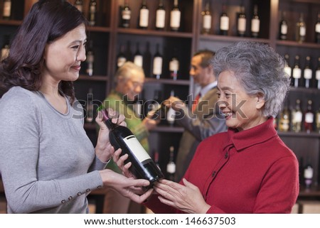 Two Women Examining Wine at a Wine Store - stock photo