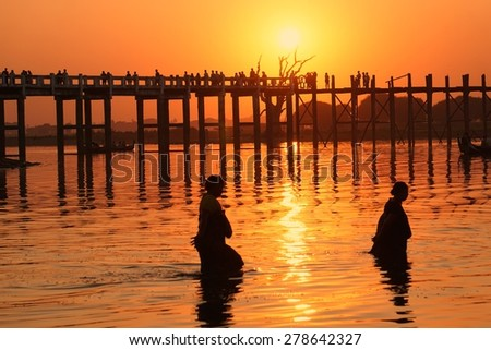 Two women fishing in Irrawaddy near U Bein wooden bridge Mandalay at sunset - stock photo