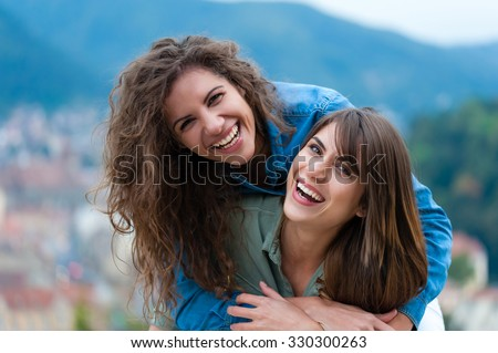 Two women friends laughing and hugging outdoors.  - stock photo