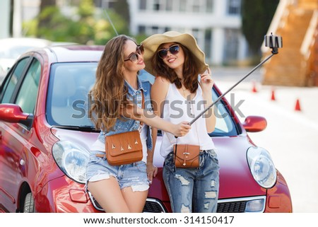 two women friends making self portrait using selfie stick near car. vacation concept. holidays, tourism and modern technology concept - smiling girls taking selfie with smartphone camera in the city - stock photo