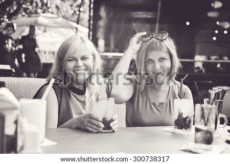 two women friends sitting in outdoor cafe - stock photo