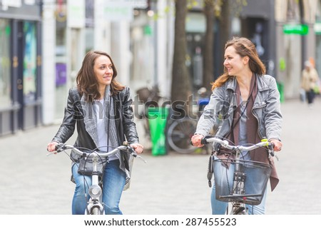 Two women going by bike in Copenhagen. They are in their twenties and they are wearing smart casual clothes. Bicycles are a typical mode of transport in Denmark. - stock photo