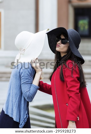 Two women greet each other with kiss - stock photo