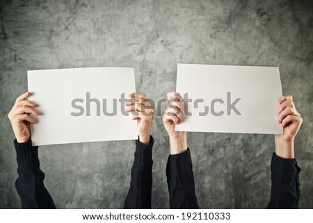 Two women holding blank paper posters above their heads - stock photo
